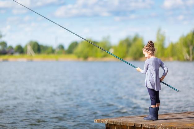 Menina bonitinha em botas de borracha, pesca do cais de madeira em um lago.