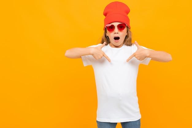 Menina bonitinha em camiseta branca, óculos de sol vermelhos e chapéu vermelho gesticulando e sorri na câmera isolada no branco