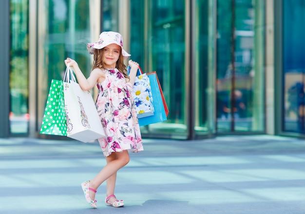 Menina bonitinha em compras. retrato de uma criança com sacolas de compras. compras. menina.