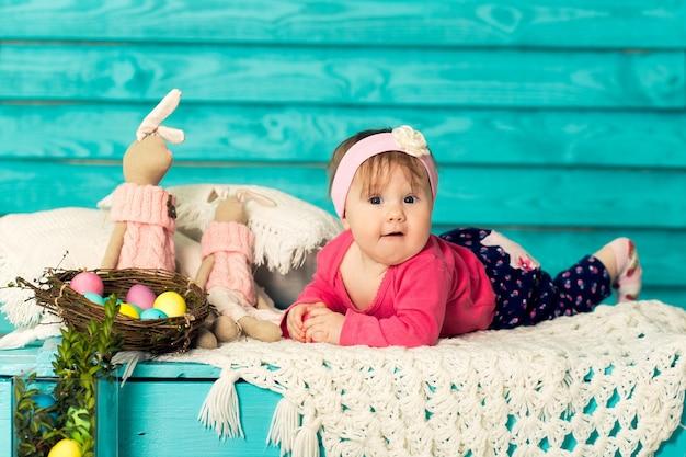 Menina bonitinha em decorações de páscoa com parede de madeira azul no fundo.