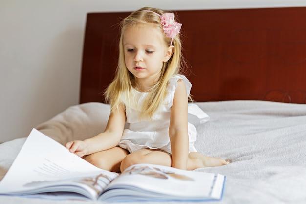 Menina bonitinha em elegante vestido branco, lendo um livro