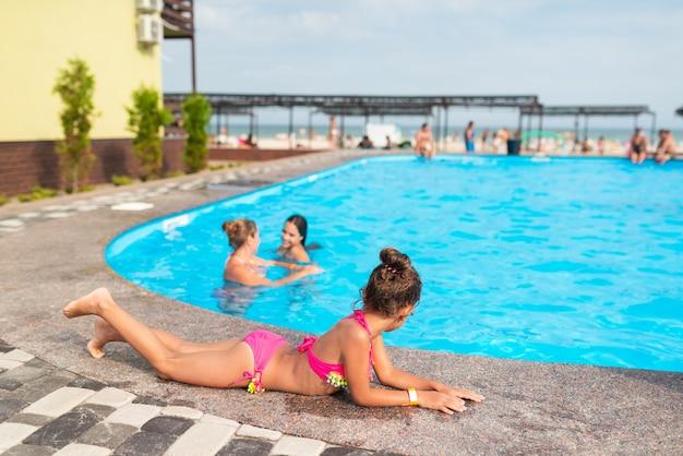 Menina bonitinha em maiô rosa encontra-se na beira da piscina e se bronzear sob os raios brilhantes do sol em um dia ensolarado de verão durante as férias. turismo e conceito de viagens. espaço de publicidade