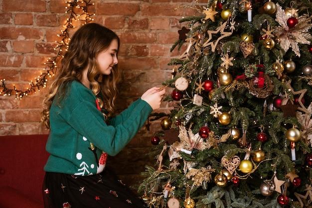 Menina bonitinha em malha verde renas do norte suéter caucasiana, menina, decora uma árvore de natal.