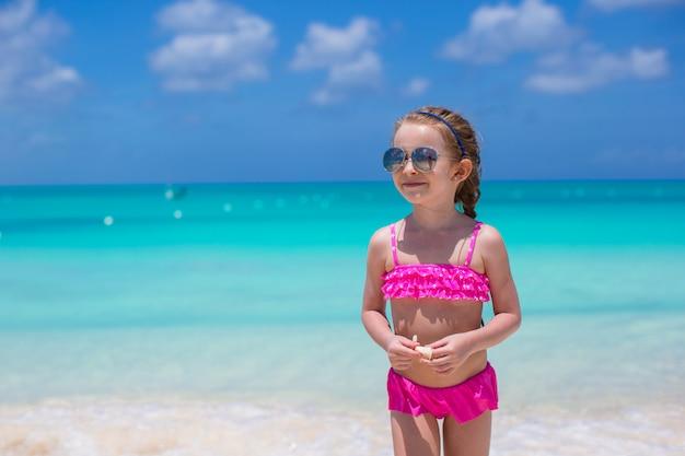 Menina bonitinha em óculos de sol na praia durante as férias de verão
