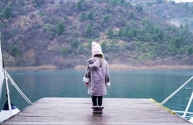 Menina bonitinha em pé no cais de madeira perto do lago turquesa