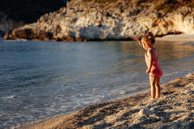 Menina bonitinha em pé perto do mar