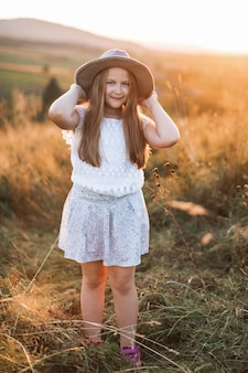 Menina bonitinha em roupas brancas e chapéu marrom fica no campo de verão na sunset