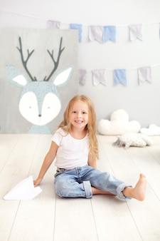 Menina bonitinha em roupas casuais joga no jardim de infância, detém um avião de papel. crianças, diversão, jogos, atividades e tempo livre. uma criança no quarto das crianças está brincando. o conceito de infância. balão