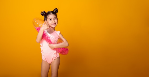 Menina bonitinha em traje de banho e anel inflável de natação sorrindo sobre fundo amarelo. banner copyspace.