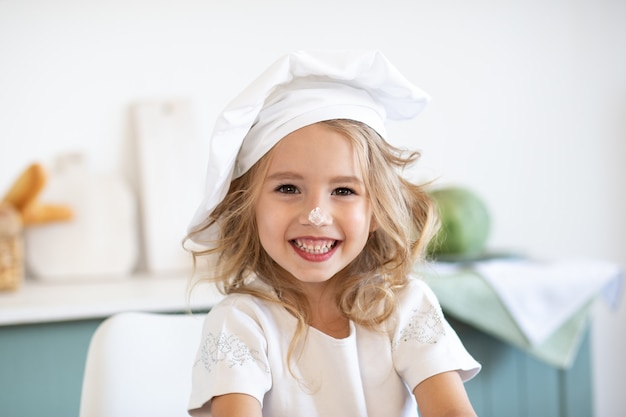 Menina bonitinha em traje de cozinheiro