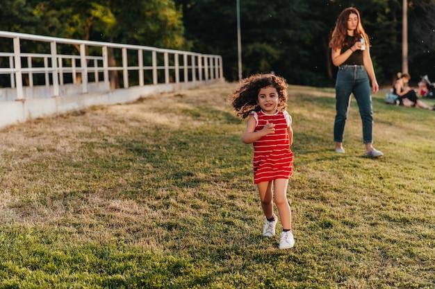 Menina bonitinha em traje vermelho correndo no parque. criança encantadora com cabelo encaracolado, brincando no gramado.