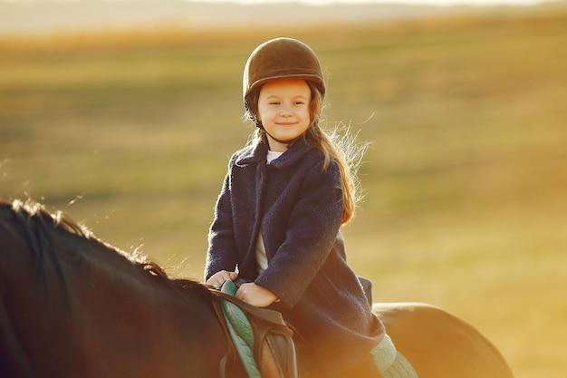 Menina bonitinha em um campo de outono com cavalo