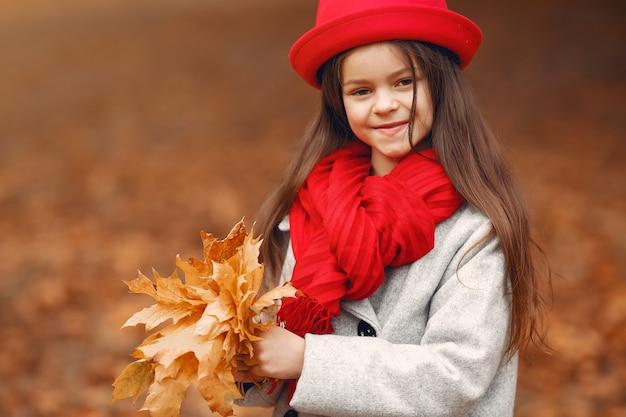 Menina bonitinha em um casaco cinza, jogando em um parque de outono