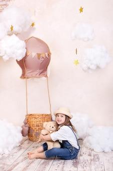 Menina bonitinha em um chapéu abraça um ursinho de pelúcia. criança brinca no quarto das crianças com um brinquedo.