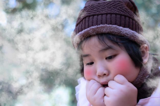 Menina bonitinha em um chapéu de lã com o tempo está frio