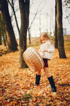 Menina bonitinha em um parque de outono