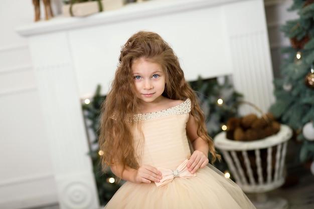 Menina bonitinha em um vestido bege exuberante posando perto da árvore de natal