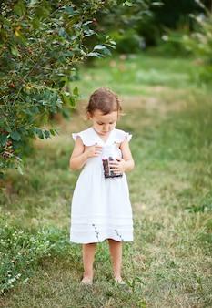 Menina bonitinha em um vestido branco, colhendo uma cereja em um jardim e come. tempo de colheita.