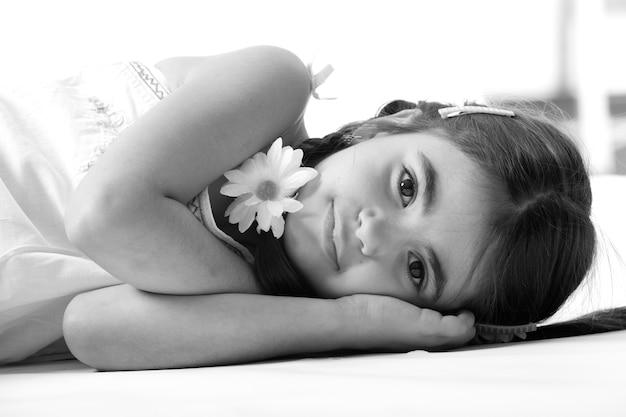 Menina bonitinha em um vestido branco, sorrindo e deitada no chão, descansando a cabeça nas mãos. foto em fundo branco