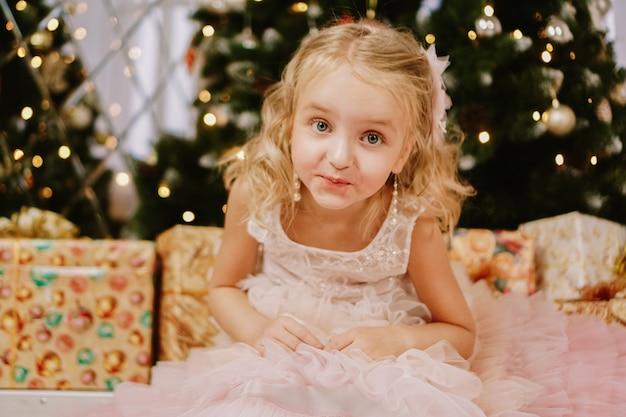 Menina bonitinha em um vestido rosa com um presente na árvore de natal de fundo