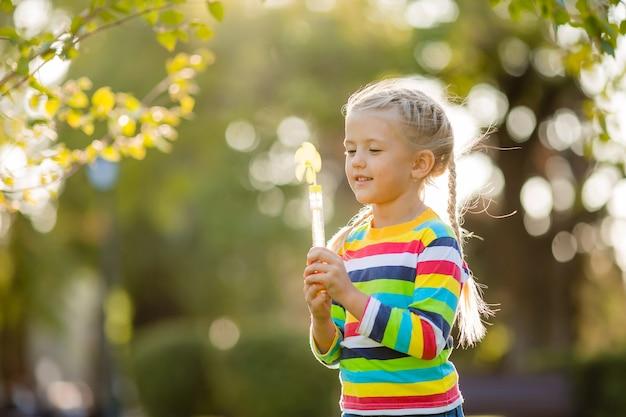 Menina bonitinha em uma caminhada com uma blusa de malha multicolorida