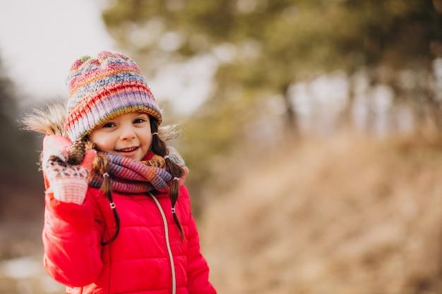 Menina bonitinha em uma floresta de inverno