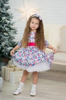 Menina bonitinha em uma pose bonita perto da árvore de natal