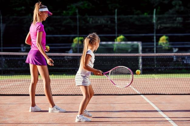 Menina bonitinha em uniforme branco, batendo a bola sob a rede durante o treinamento de tênis com o treinador. treinador feminino atraente fazendo exercícios com pouco tenista na quadra ao ar livre ao pôr do sol.