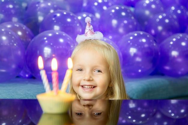 Menina bonitinha em vestido elegante, comemorando o dia do aniversário com balões roxos