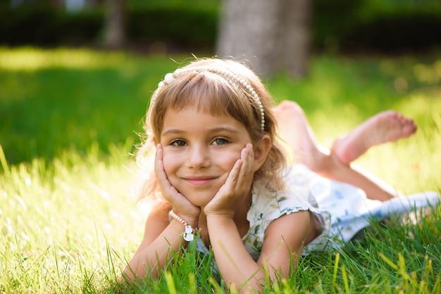 Menina bonitinha encontra-se na grama no parque de verão