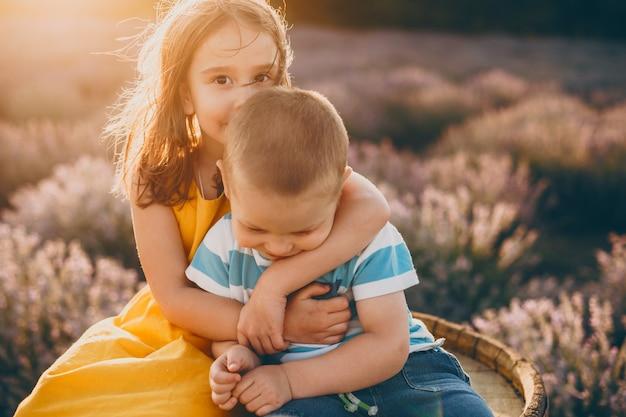 Menina bonitinha enquanto beija seu irmão mais novo e o abraça contra o pôr do sol em um campo de flores.