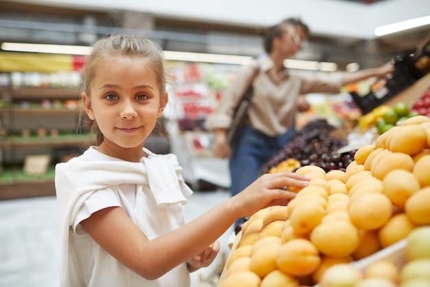 Menina bonitinha escolhendo frutas