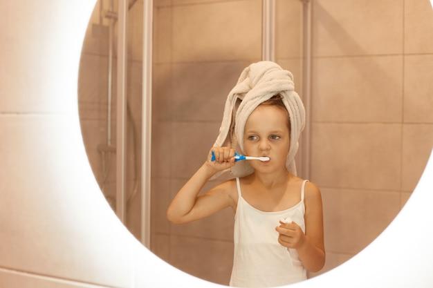 Menina bonitinha escovando os dentes no banheiro em pé na frente do espelho, vestindo camiseta branca sem mangas e enrolou o cabelo na toalha, procedimentos higiênicos matinais.