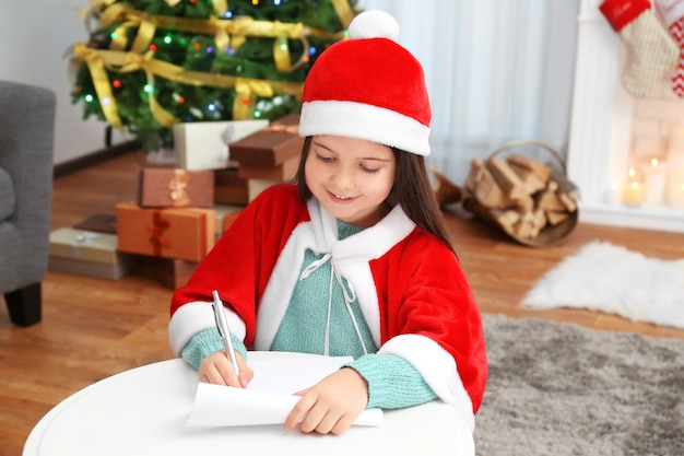 Menina bonitinha escrevendo carta para o papai noel na mesa