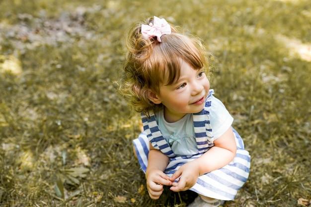 Menina bonitinha está brincando com folhas no outono park
