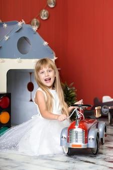 Menina bonitinha está brincando com um caminhão de bombeiros de brinquedo grande. infância feliz.