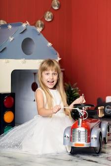 Menina bonitinha está brincando com um caminhão de bombeiros de brinquedo grande