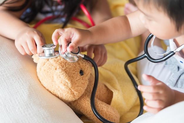 Menina bonitinha está brincando de médico com estetoscópio e ursinho de pelúcia.