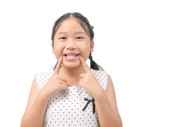 Menina bonitinha está sorrindo alegre mostrando e apontando com os dentes dos dedos e a boca isolada no fundo branco. conceito de saúde bucal.
