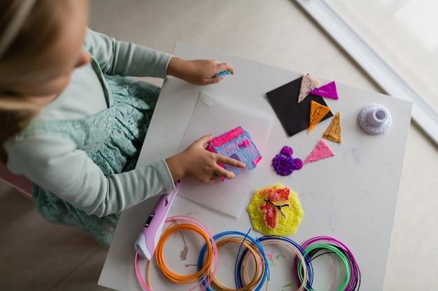 Menina bonitinha faz uma casa de plástico, desenha peças com uma caneta 3d. desenvolvimento, modelagem, educação, design com plástico quente. tecnologias modernas. faça você mesmo.