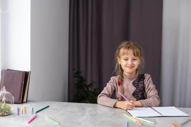 Menina bonitinha fazendo a lição de casa, close-up, no fundo do interior da casa