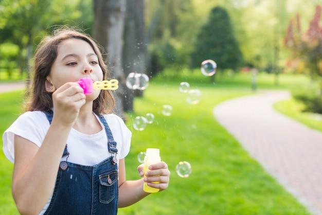 Menina bonitinha fazendo bolhas de sabão