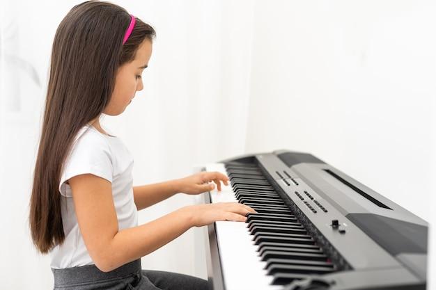 Menina bonitinha fazendo curso de treinamento com piano