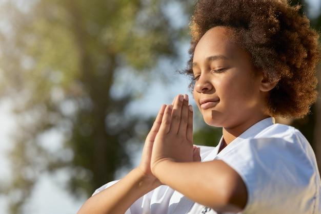 Menina bonitinha fazendo exercícios de meditação ao ar livre