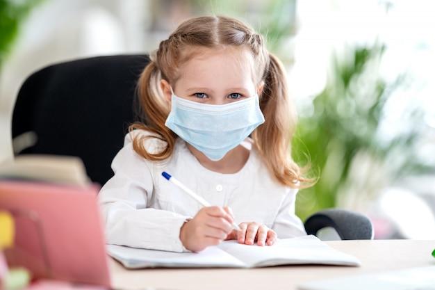Menina bonitinha, fazendo lição de casa, escrevendo no caderno, usando laptop, e-learning