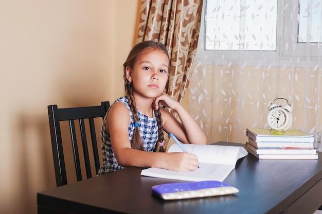 Menina bonitinha fazendo lição de casa, lendo um livro, escrevendo e pintando.