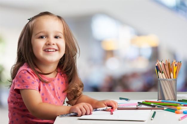 Menina bonitinha fazendo lição de casa, lendo um livro, páginas para colorir, escrevendo e pintando.