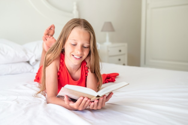 Menina bonitinha fazendo lição de casa no laptop