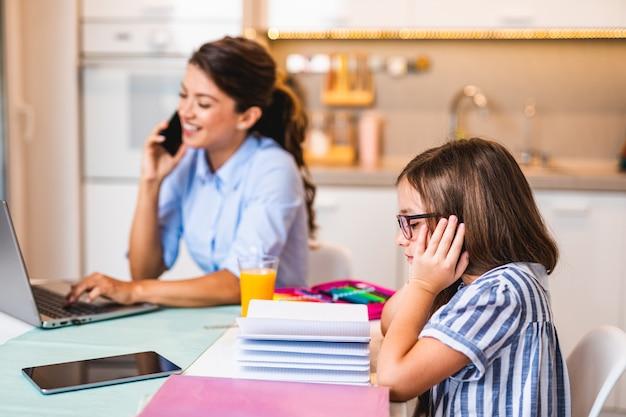 Menina bonitinha fazendo sua lição de casa, enquanto sua mãe trabalhava em casa devido a uma pandemia de coronavírus.