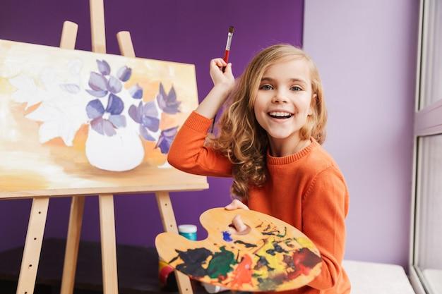 Menina bonitinha fazendo um desenho em uma tela dentro de casa